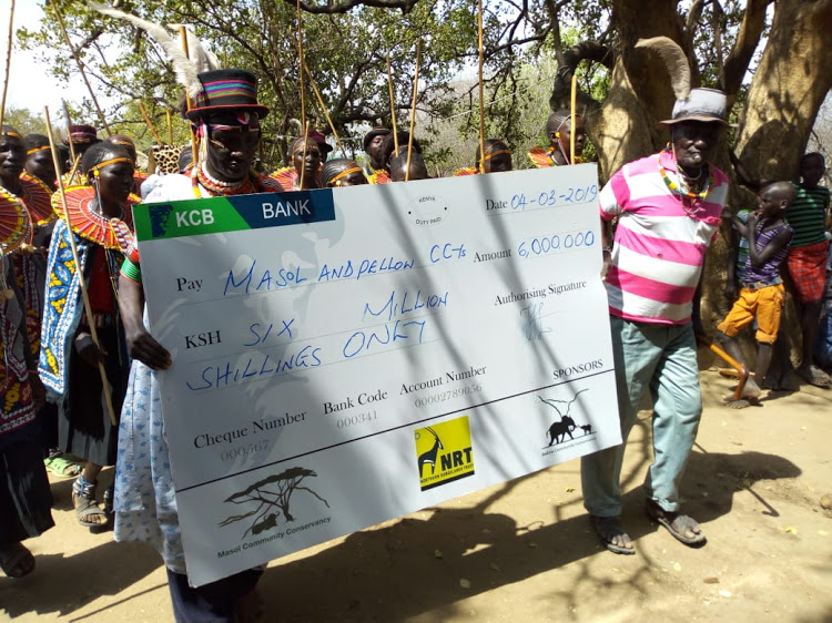 Elders from Masol Community display a dummy cheque