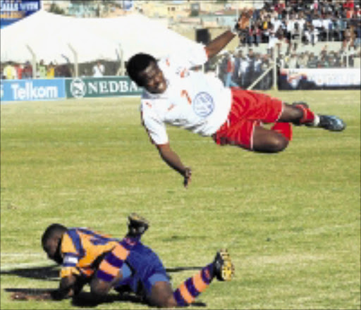 IN FULL FLIGHT: Siyabulela Songwiqi, airborne is tackled by Elasto Kapowenzha during the National First Division final match between Bay United and FC AK at Woolfson's Stadium in Port Elizabeth. Pic. Lee Warren. 13/07/2008. © Gallo Images