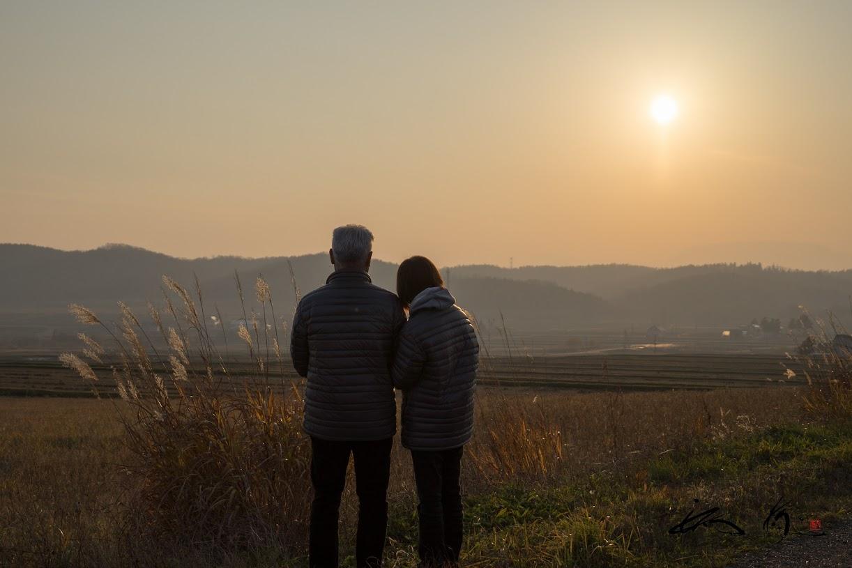 初冬の夕暮れ、オレンジ色の空を二人で眺めながら