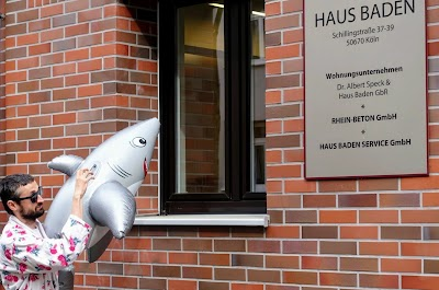 Vor Haus Baden: Demonstrant im Bademantel lässt Bade-Hai ins Fenster gucken.