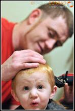 Photo: John gives his son Steven a haircut.