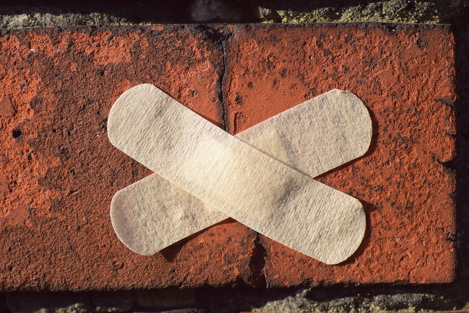 Two pieces of tape fixing a cracked brick