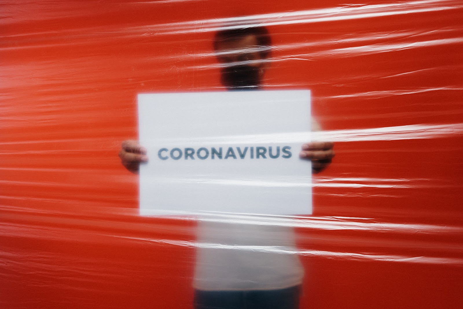 An anxious person showing Coronavirus message on a board signifying importance of how to cope with anxiety