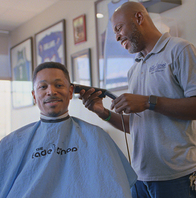 man cutting man's hair with hair clippers in barbershop
