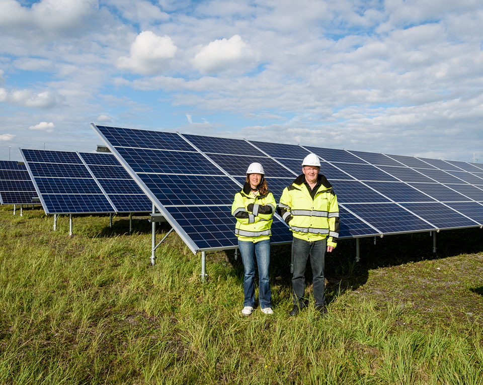 Man and woman standing in front of solar panels