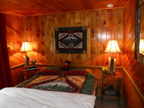 Photo: Cozy down comforters, Adirondack decor in woodsmoke suite. The wall of windows on the left face the lake.