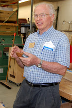 Photo: Phil Brown show a mini vortex bowl that he made, as a fund raiser for the Center for Art in Wood, from the core of a bowl made by Robin Wood on a pole lathe.