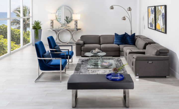 Large living room with blue accent colors and blue accent chairs. Wall art and coffee table shown in the room.