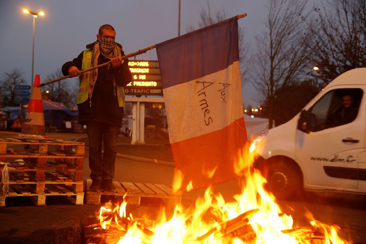 A protester wearing a yellow vest, the symbol of a French drivers' protest against higher diesel fuel prices, holds a flag near burning debris at the approach to the A2 Paris-Brussels Motorway, in Fontaine-Notre-Dame, France, on December 4 2018. Picture: REUTERS/PASCAL ROSSIGNOL