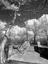 Photo: Black and white photo of a stone bridge and trees and clouds at Eastwood Park in Dayton, Ohio.