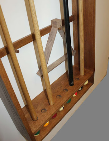 a wall mounted cue rack with pool cues and balls