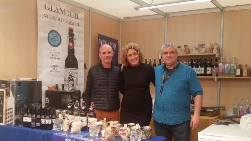 José Antonio Moya (a la derecha) junto a dos colaboradores en un stand de degustación, Al lado, un cartel de su vermut.
