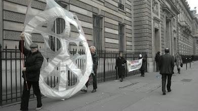 Photo: le grand logo du désarmement nucléaire se promène devant les grilles...