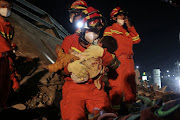 A rescue worker carries a child from the site where a hotel being used as a coronavirus quarantine site collapsed, in the southeast Chinese port city of Quanzhou, Fujian province, China, on March 8 2020.