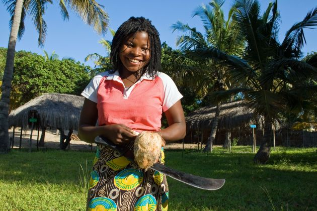 A Mozambique woman opens a coconut with a machete close to the beach