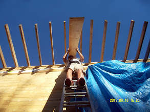 Photo: Owner/designer-guy helps move the light-as-a-feather pine decking to the roof.