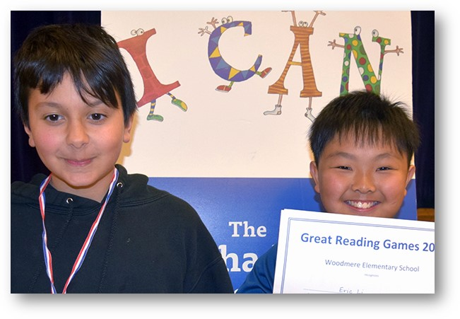 Two young boys proudly displaying their Great Reading Game awards.  One has a grin and a medal around his neck.  The other is smiling widely and holding up his GRG certificate