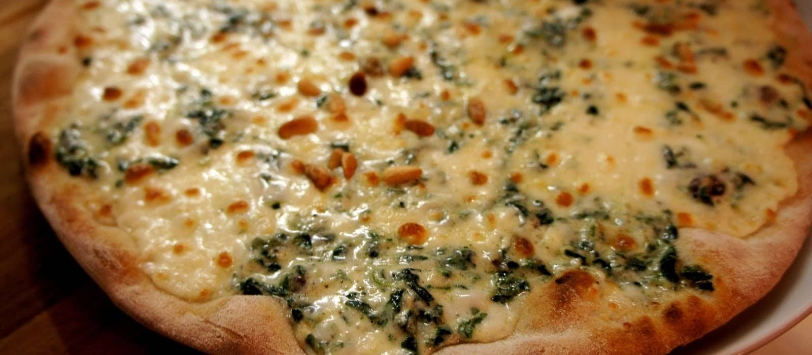 Signature pizza with burrata cheese, spinach and pine nuts.