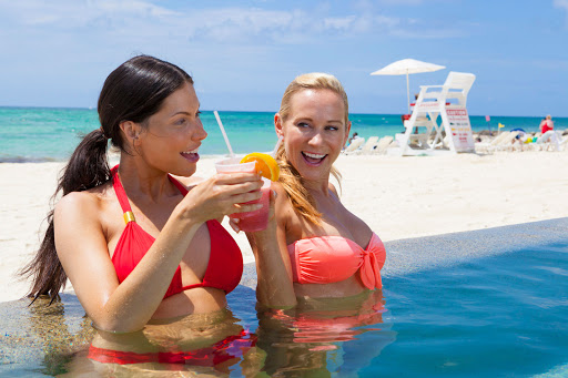 Two women celebrate happy hour in the pool at the Grand Lucayan Resort on Grand Bahama Island.