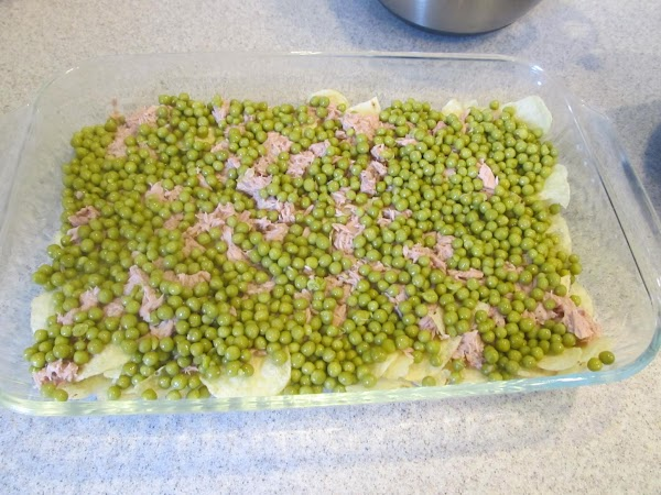 Now take a spoon and begin layering the garden peas on the chips. Next, you...