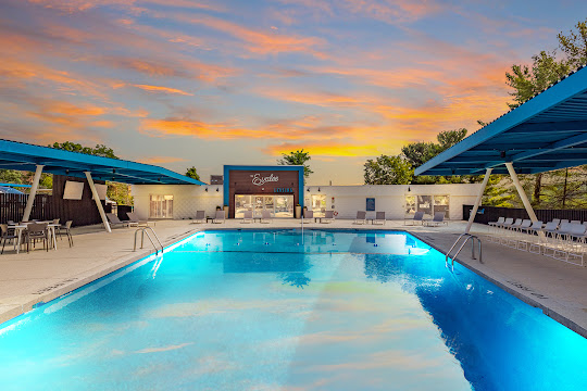 The Evalee's swimming pool with lounge chairs, next to the clubhouse, at dusk