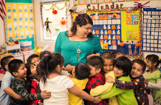 Smiling woman in a school classroom surrounded by a group of young children.