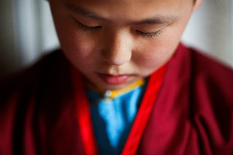 Young Buddhist monk Temuulen studies religious texts shortly after waking up in his room at the Amarbayasgalant Monastery in Mongolia.