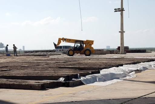 Construction crews lay wooden mats on top of sand and reinforcing steel to protect the concrete during deconstruction.