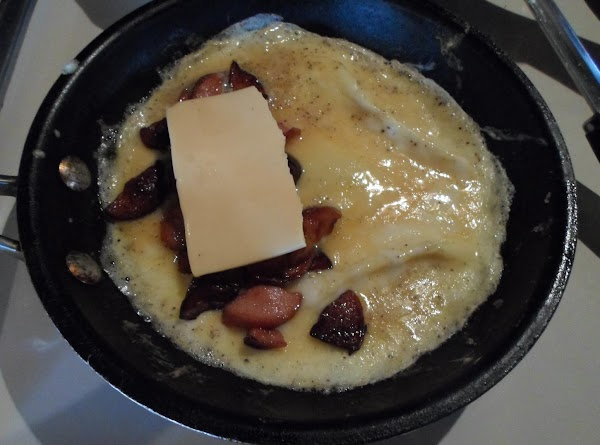 Add the hotdogs and 1/2 slice of cheese to one side of omelet, take...