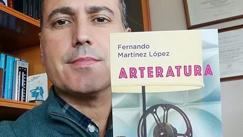 El escritor muestra un ejemplar de su nuevo libro.