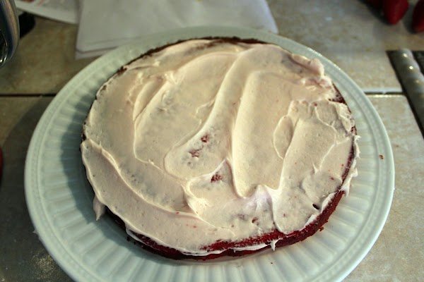 After cake has cooled, frost bottom layer.