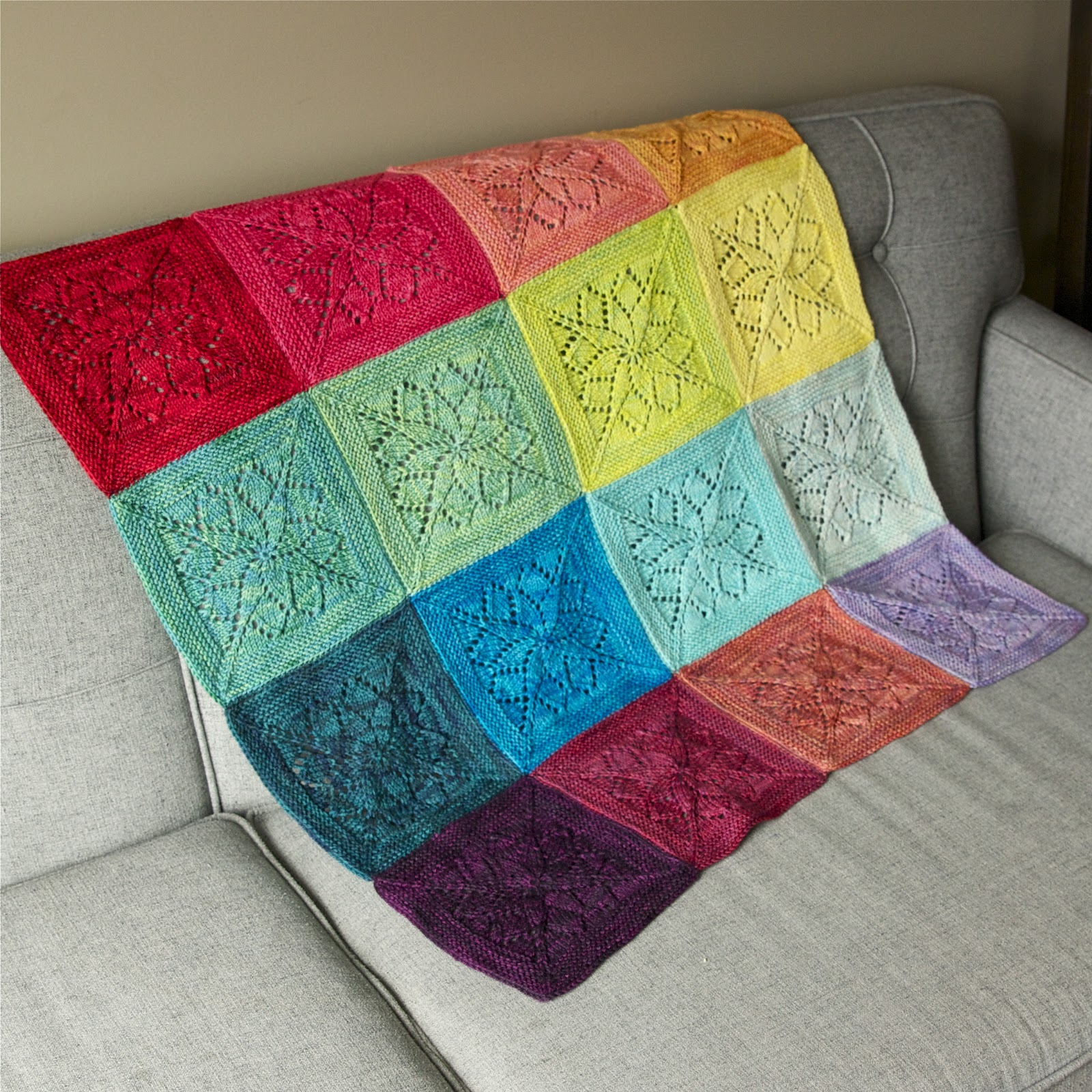 A blanket of lace squares lies over a gray couch in a rainbow of colors.