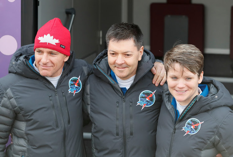 The International Space Station (ISS) crew members David Saint-Jacques of Canada, Oleg Kononenko of Russia and Anne McClain of the US walk from a hotel for a pre-launch preparation at the Baikonur Cosmodrome, Kazakhstan December 3, 2018.