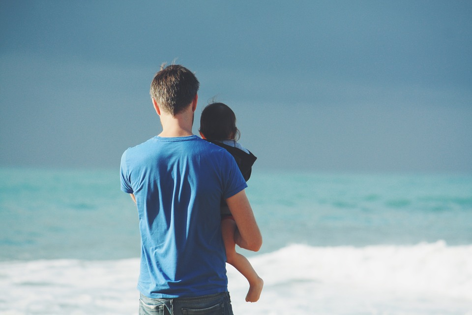 a father holding his child near the ocean