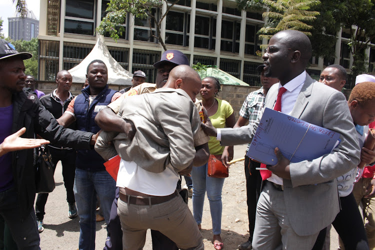 A court orderly rescues lawyer Simon Mburu from Ekeza Sacco members outside a Milimani court, Nairobi, on Thursday