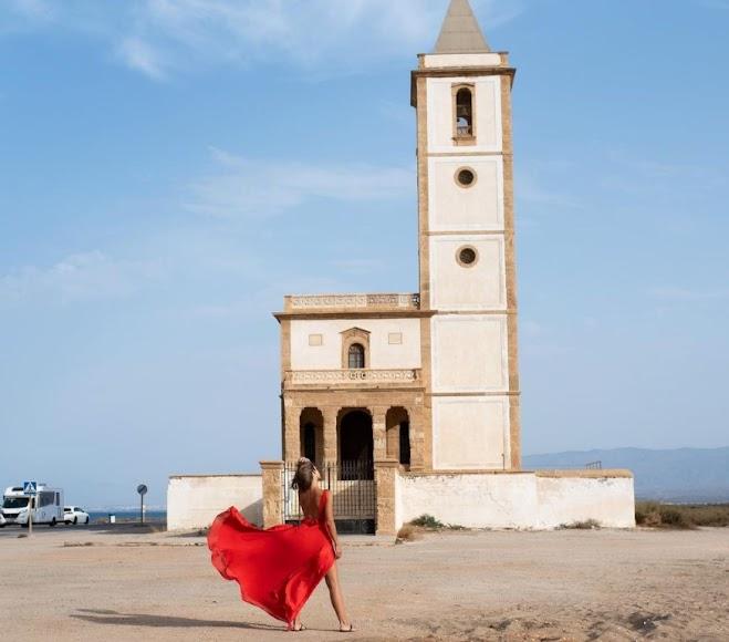 Zapater, vestida de rojo junto a la Iglesia de Las Salinas de Cabo de Gata.