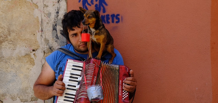 A busker and his dog work the old Alfama neighbourhood in Lisbon, Portugal