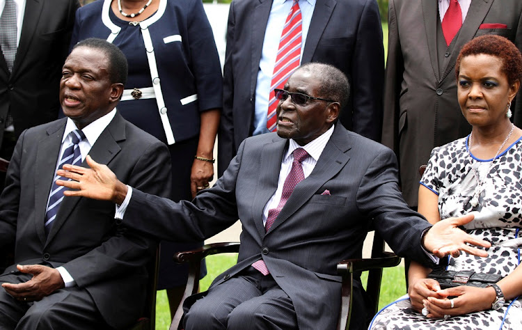 Robert Mugabe (C) sits with his wife Grace Mugabe and Emmerson Mnangagwa (L) at the State House in Harare, December 12, 2014.