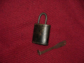 Photo: A simple Viking style padlock and key. The key slides in over a spring loaded tongue which allows the hasp to be withdrawn.