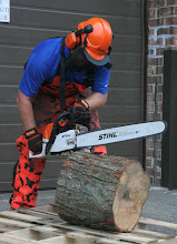 Photo: Safety gear in place, Matt has rotated the log segment into proper side-grain cutting orientation and stabilized it on a pallet.  First, he sets the spurs into the end of the log to stabilize the saw.  Make note of his firmly-balanced stance with the saw completely under control and offset to the side of his head.