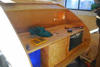 Photo: Galley Kitchen ready for finishing details and wiring. The big rectangular hole is for the power box, other holes for USB, 12V and wall outlet.