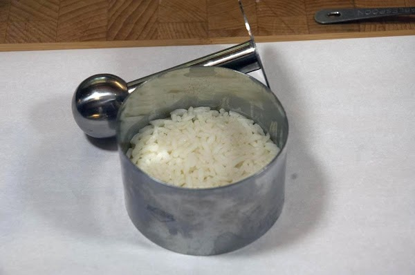 Add about 3/4 of an inch (2cm) of rice to the tower, and press...