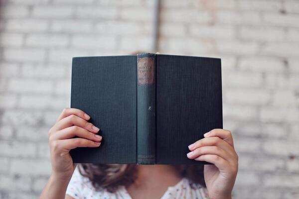 Uma pessoa segurando um livro aberto em frente a seu rosto