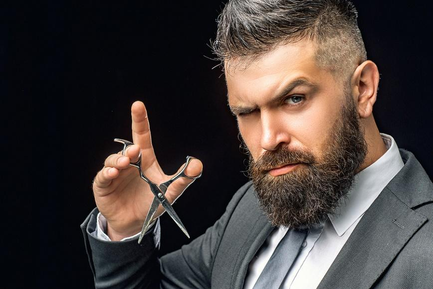 A person with a beard and a cigarette in his hand  Description automatically generated with low confidence