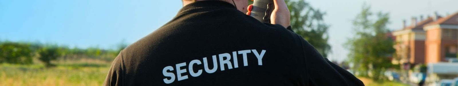 a security guard wearing a jacket that says security talking into a walkie talkie