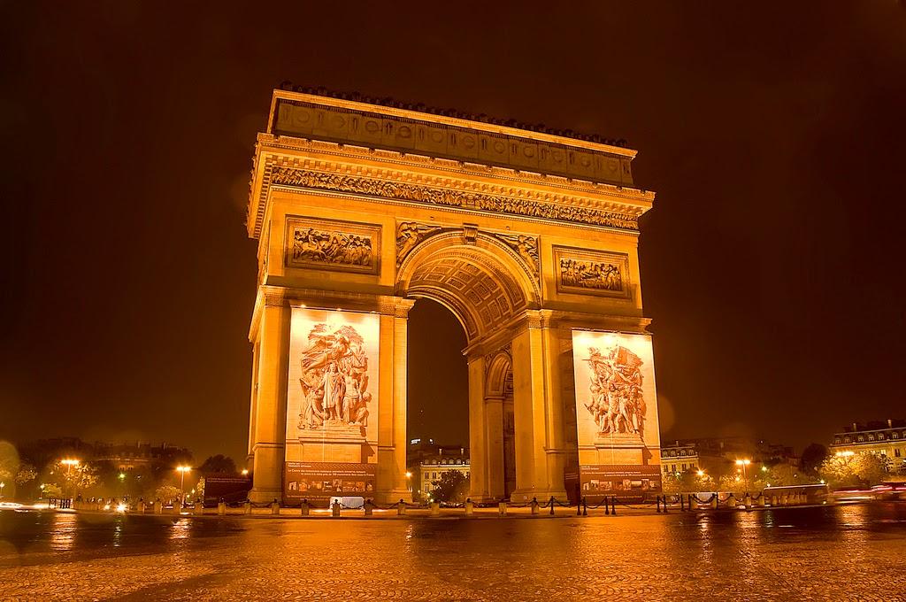 Триумфальная арка на Елисейских Полях сияет в лучах прожекторов