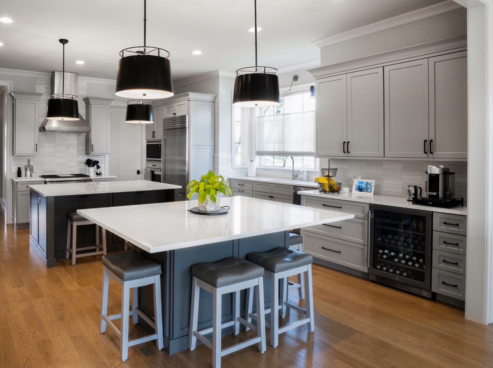 Modern Kitchen with dual islands and drum pendants. Featuring white cabinetry and countertops with contrasting gray island bases. Features a large beverage fridge  along with stainless steel appliance and range top hood.