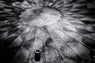 Photo: Following up on my previous post concerning 'Strawberry Fields' in Central Park, I offer this image of the 'Imagine' mosaic. This is the thing that most of the tourists crowd around when the visit the site. I shot this mid-morning on a Friday and at that time the only thing on the mosaic was this single candle. I had read that every year Yoko puts a candle at this location, but I suspect this was put there by someone else. The next day the candle was gone, replaced by a bunch of flowers arranged in the shape of a peace sign.