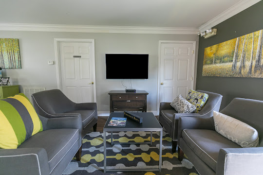 Clubhouse lounge area with dark gray chairs and TV