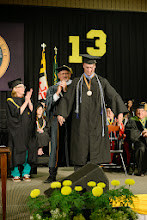 "Photo: President Roger Casey officially ""invests"" senior Tyler Justice with academic regalia to symbolize the completion of the undergraduate degree."